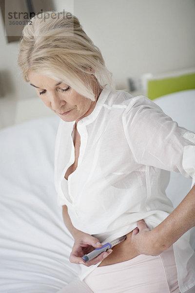 Frau spritzt sich mit einem Insulin-Pen in den Magen