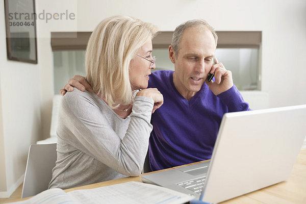 Paar sitzt zusammen vor einem Laptop