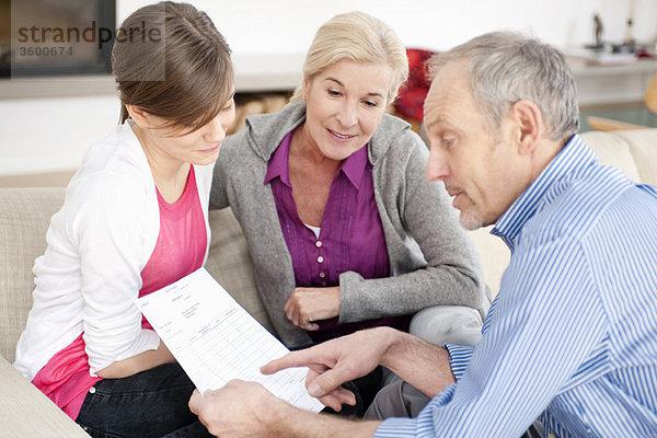 Mann, der seiner Enkelin ein Dokument erklärt.