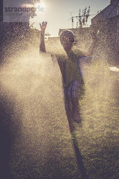 Junge hat Spaß mit Spritzwasser im Garten