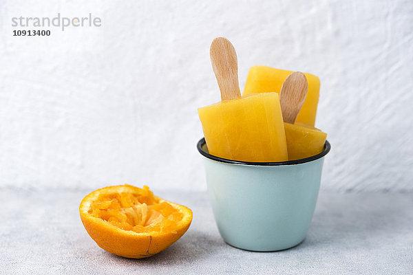 Emailleschale mit hausgemachten Orangeneis und einer gepressten Orangenschale