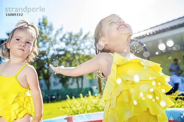 Zwei kleine Schwestern im Planschbecken im Garten