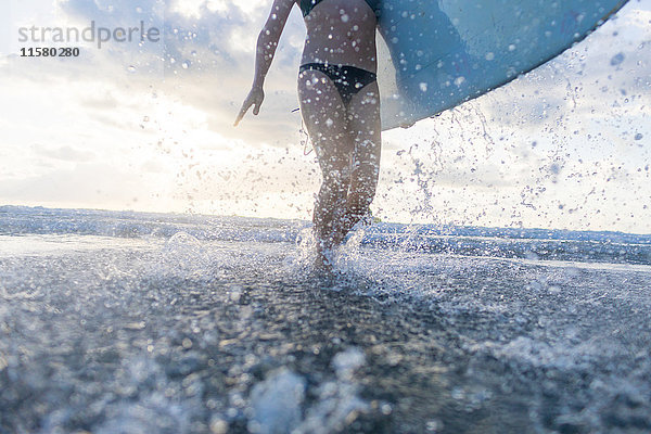 Nackenansicht einer Frau, die ein Surfbrett trägt und im Meer planscht, Nosara, Provinz Guanacaste, Costa Rica