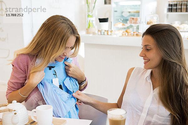 Junge Frau zeigt neu gekaufte Bluse beim Entspannen im Cafe mit Freundin