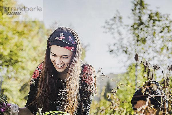 Glückliche junge Frau beim Gärtnern