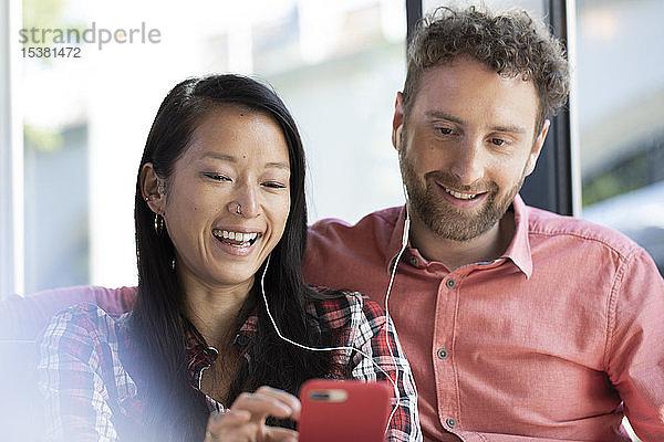 Glücklicher Mann und glückliche Frau mit Handy und Ohrstöpseln in einem Cafe