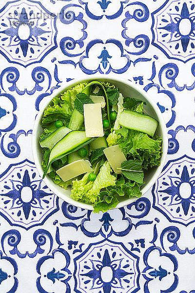 Draufsicht auf Erbsen- und Gurkensalat auf gemustertem Tisch