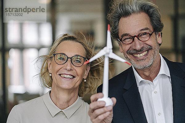 Porträt eines glücklichen Geschäftsmannes und einer glücklichen Geschäftsfrau mit einem Modell einer Windkraftanlage im Amt