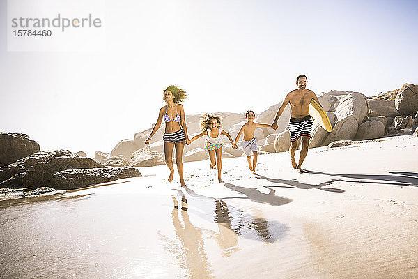 Glückliche Familie läuft am Strand