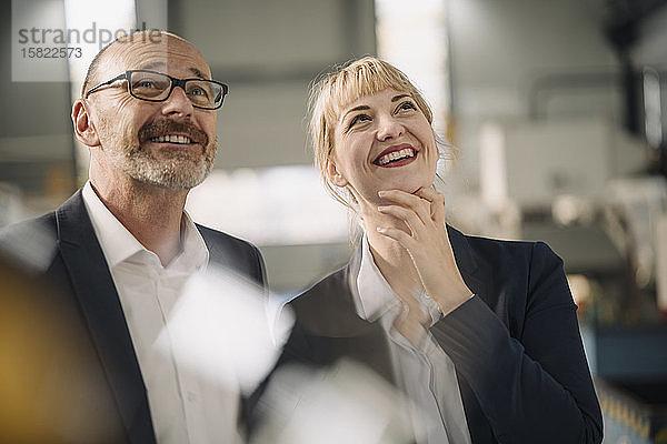 Porträt eines glücklichen Geschäftsmannes und einer glücklichen Geschäftsfrau in einer Fabrik mit Blick nach oben