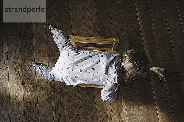 Rückenansicht eines auf einem Stuhl liegenden Kleinkindes, Draufsicht