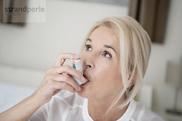 Nahaufnahme einer Frau mit einem Asthma-Inhalator