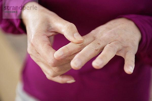 Nahaufnahme einer Frau mit Fingerschmerzen