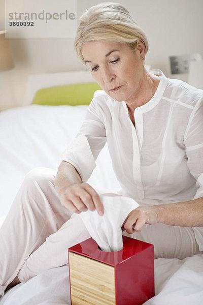 Frau holt Seidenpapier aus einer Schachtel heraus