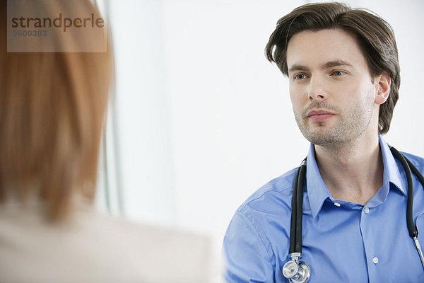 Arzt sieht eine Frau an