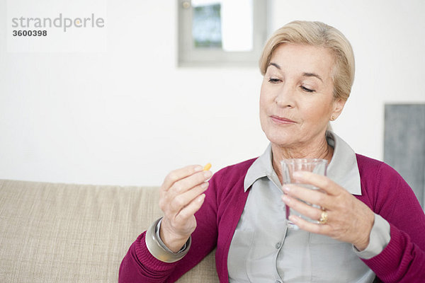 Frau nimmt eine Kapsel