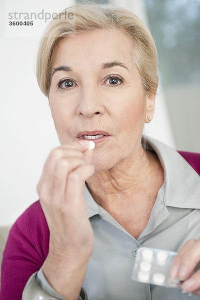 Nahaufnahme einer Frau bei der Einnahme von Medikamenten