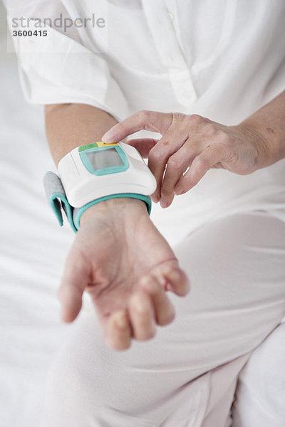 Frau überprüft ihren Blutdruck