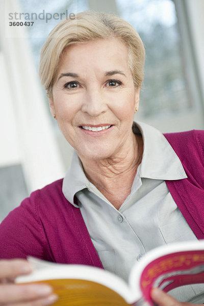 Porträt einer Frau, die ein Buch hält und lächelt