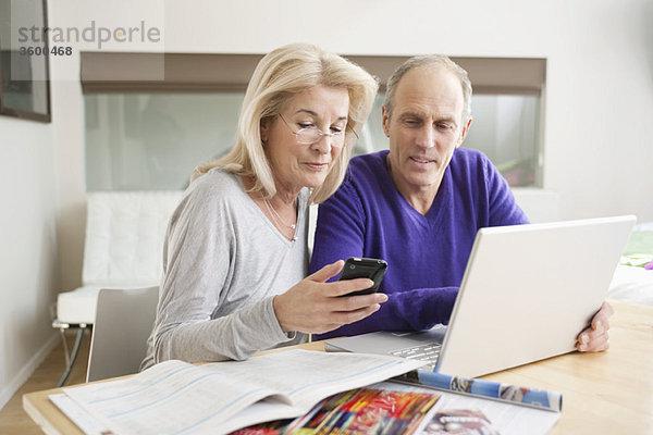 Frau Textnachrichten auf einem Handy mit ihrem Mann neben ihr sitzend