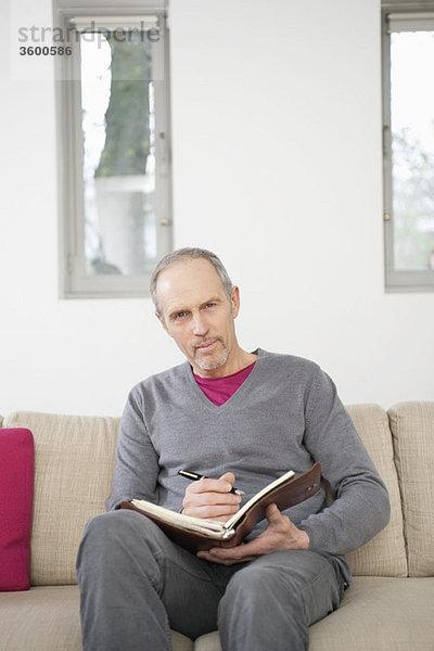 Porträt eines Mannes, der in einem Terminplaner schreibt