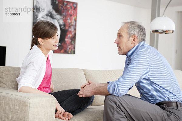 Mädchen sitzend mit ihrem Großvater