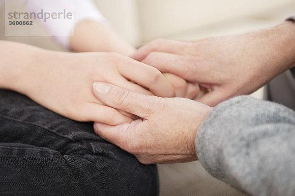 Frau hält die Hände ihrer Enkelin