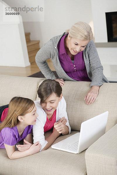 Zwei Mädchen, die mit ihrer Großmutter einen Laptop auf einer Couch benutzen.