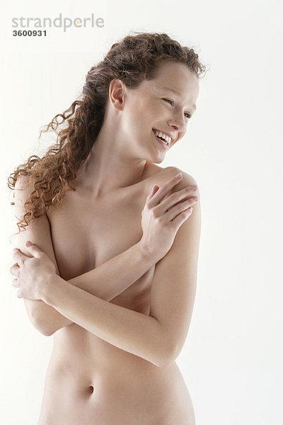Nackte Frau, die sich umarmt und lächelt.