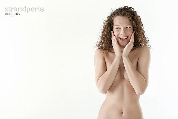 Nahaufnahme einer Frau, die ihre Wangen berührt und lächelt