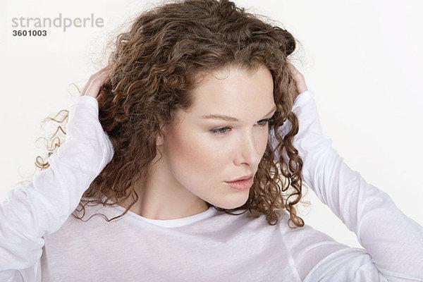 Nahaufnahme einer Frau mit Händen im Haar