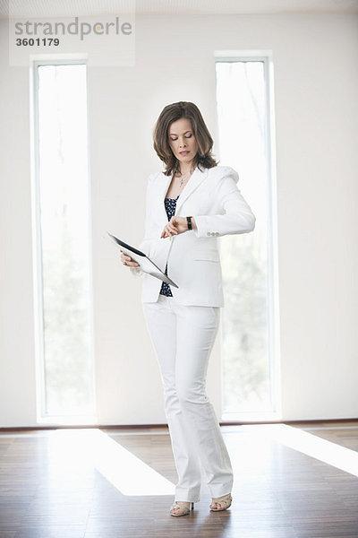 Geschäftsfrau, die ein Dokument hält und die Zeit prüft
