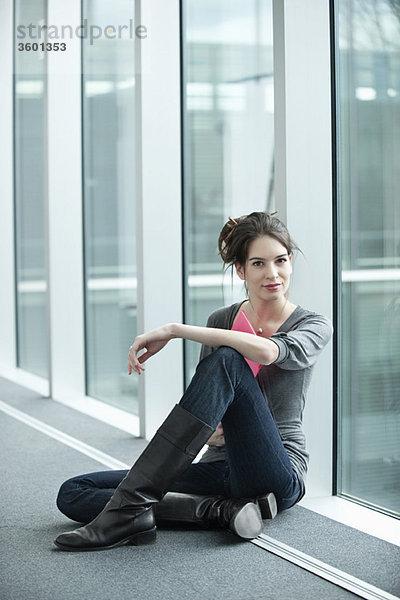Geschäftsfrau, die eine Akte hält und in einem Büroflur sitzt.