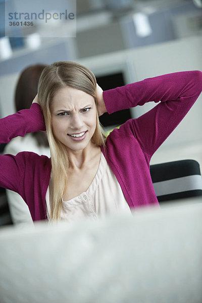 Geschäftsfrau hält sich im Büro die Ohren zu.