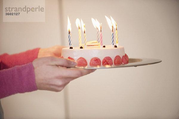 Nahaufnahme der Hände einer Frau, die einen Geburtstagskuchen hält.