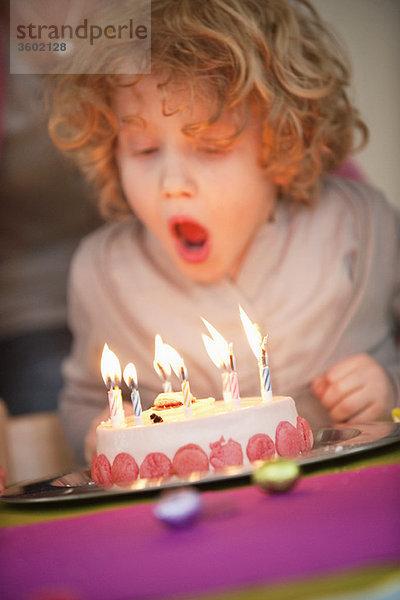 Junge, der Kerzen auf seinem Geburtstagskuchen ausbläst.