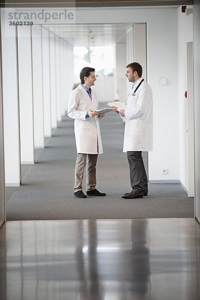 Zwei männliche Ärzte diskutieren über die