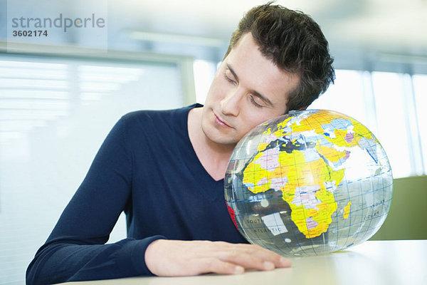 Geschäftsmann schlummert auf einem Globus in einem Büro
