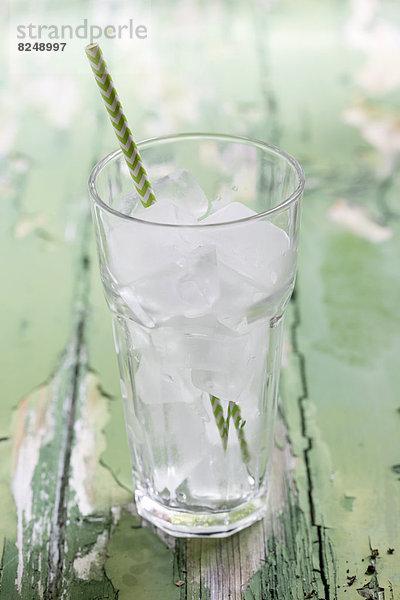 Glas Eiswürfel mit Trinkhalm auf Holztisch, Nahaufnahme