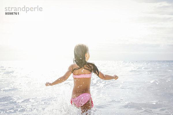 Rückansicht des Mädchens beim Laufen und Plantschen im Meer, Toskana, Italien