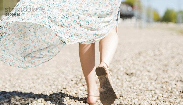 Frau geht am Kiesstrand spazieren