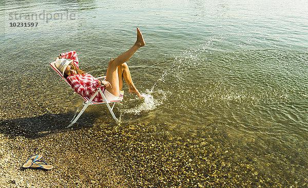 Junge Frau sitzt auf einem Liegestuhl im Fluss und spritzt mit Wasser.