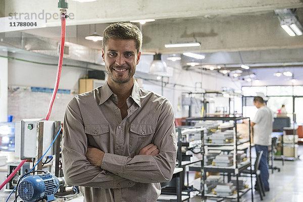 Mann lächelt in der Werkstatt, Portrait