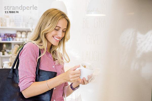 Frau schaut Kaffeetasse im Geschäft an