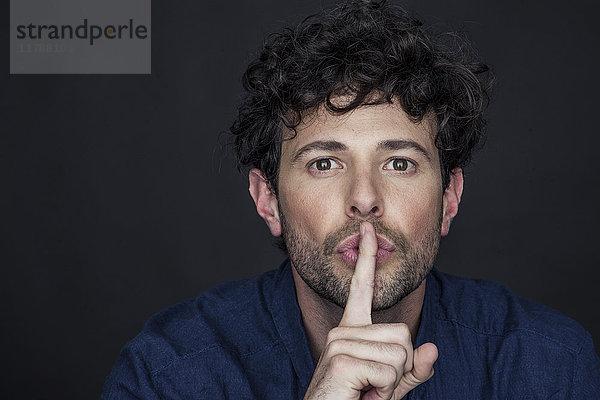 Mann, der mit dem Finger an die Lippen gehalten wird.