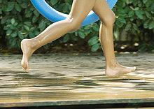 Kind läuft am Beckenrand, abgeschnittene Ansicht der Beine