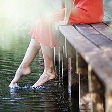 Junge Frau am Fluss sitzend