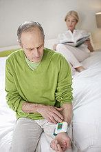 Ein Mann, der seinen Blutdruck mit einer Frau im Hintergrund überprüft.