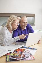 Paar schaut auf einen Laptop und lächelt