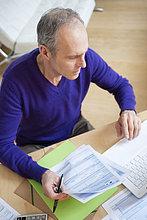 Mann mit Steuerformularen und Laptop